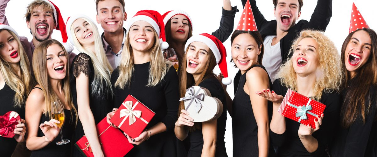 Happy Christmas people. Isolated. Group friends in black classic clothes with gifts and a Santa hats.